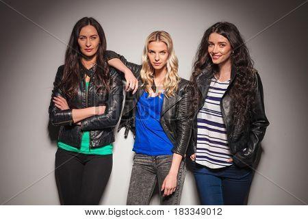 three women frisnds posing together on grey studio wall