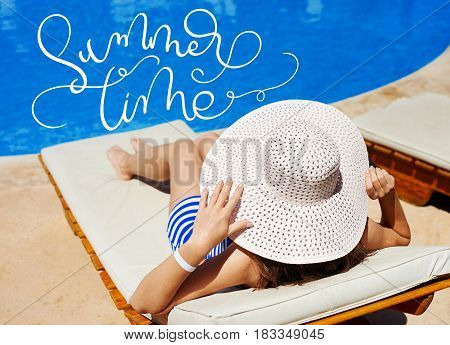 Beautiful woman in a big white hat on a lounger by the pool and text Summer time. Calligraphy lettering hand draw.
