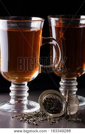 A glass of tea with a strainer on a dark background.