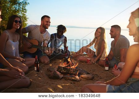 Group of friendly teenagers sitting around campfire by lake on summer evening