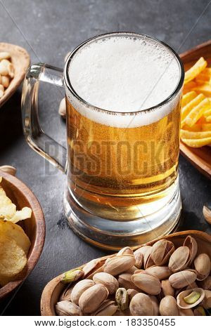 Lager beer and snacks on stone table. Nuts, chips