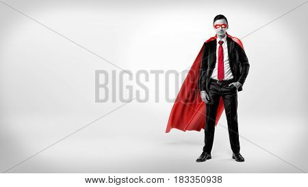 A self-assured businessman in a red cape and a mask standing with a hand in his pocket on white background. Confidence and self-worth. Motivated employees. Business and work.