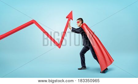 A businessman in a red flowing cape trying to bend a red statistic arrow upwards on blue background. Accounting and finance. Business and investment. Profit and loss.
