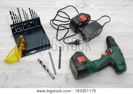 A cordless drill, a spare battery, a set of bits and yellow safety glasses on wooden table background. Handyman. Repairs and DIY. Manual work tools.
