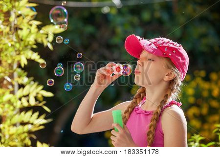 little girl blowing bubbles in summer