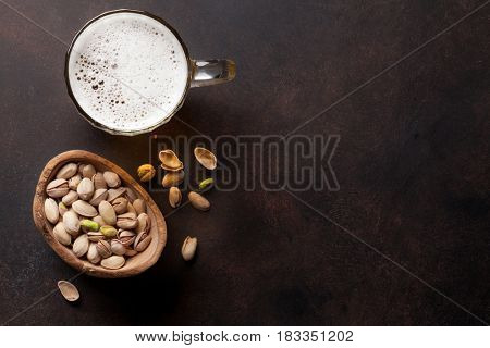 Lager beer and nuts on stone table. Top view with copy space