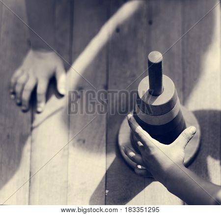 Hands holding object on wooden table