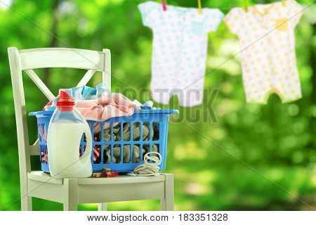 Basket with baby laundry and bottle of detergent outdoor