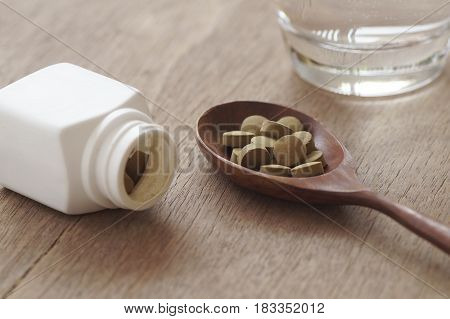 herb medicine in pill on wood table