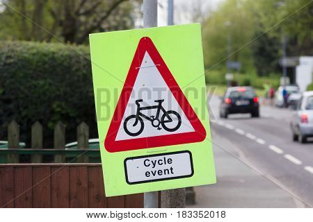 Temporary cycling event sign hung next to a busy main road warning drivers to look out for cyclists in a road race