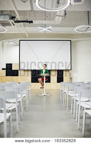 Young woman sitting by table in lecture-hall with whiteboard behind