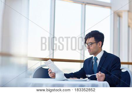 Elegant banker eating his breakfast in restaurant and reading newspaper