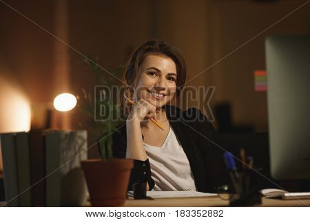Portrait of young woman designer holding glasses at her workplace