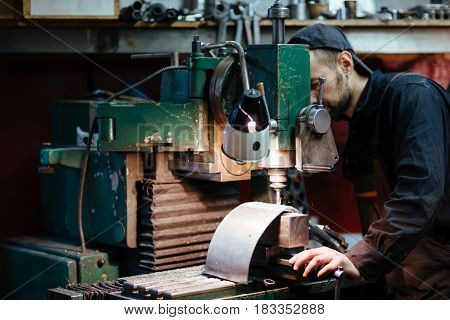 Portrait of man in workers uniform using drilling unit to make metal parts