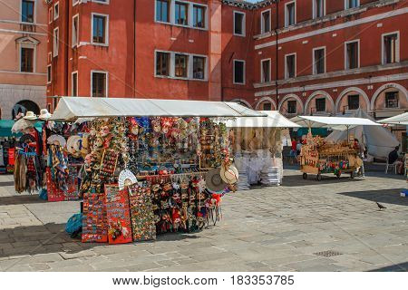 Street market with traditional venetian carnival masks at the square near Santa Maria Gloriosa dei Frari church at a beautiful sunny summer day in Italy
