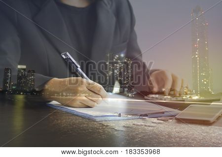 double exposure of Businesswoman Hand Calculating Invoice Using Calculator At Desk In Office and nigt city concept in finance account and capital banking