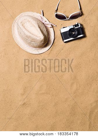 Summer vacation composition with wicker hat, sunglasses and retro styled camera laid on a beach. Sand background, studio shot, flat lay. Copy space.