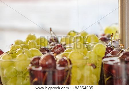 A close-up view of water drops falling on variety fresh red cherries and green grapes in a cups at local market for sale. Selected focus