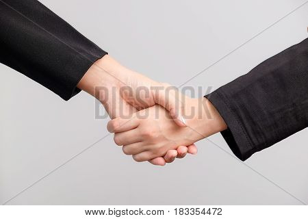 Close up of two business women shaking hand on white background