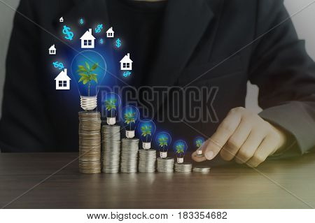 businesswomen put money on pile of coins with green tree house and light bulb concept in finance loan and buying in business about home