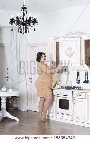 Plus size fashion model on kitchen fat woman on luxury interior overweight female body professional make-up and hairstyle