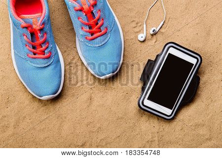 Blue sports shoes with pink shoelaces, earphones and smart phone laid on sand beach background, studio shot, flat lay.