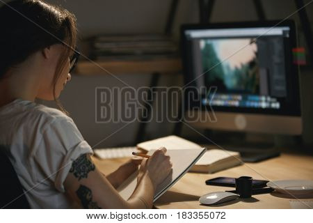 Picture of young lady designer sitting indoors at night drawing sketches in album while using computer.