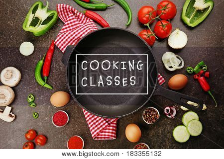 Cooking classes concept. Frying pan with fresh ingredients on gray background