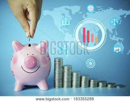 hand put money on pink of piggy bank and pile of coins on blue background concept in growth save and investment in business
