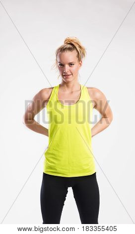 Attractive young fitness woman in yellow tank top. Studio shot on gray background.