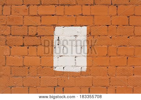 Orange brick wall with painted splotch as background or texture