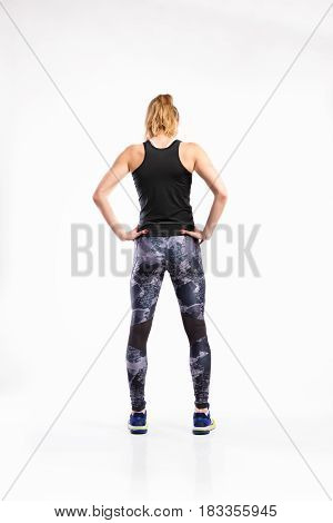 Attractive young fitness woman in black tank top and leggings, arms on hips. Studio shot on gray background. Rear view.