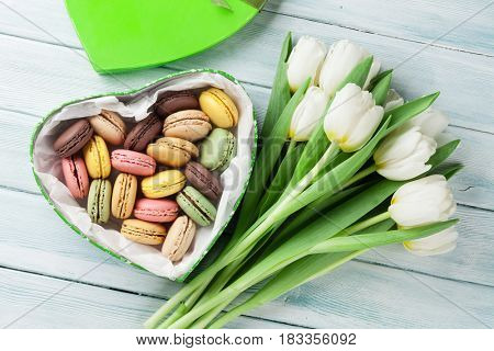 White tulips bouquet and gift box with macaroons on wooden background. Top view