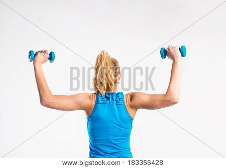Attractive young fitness woman in blue tank top, holding dumbbells. Slim waist, perfect fit female body. Studio shot on gray background. Rear view.