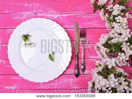 White dish with an empty paper note on a pink wooden surface top view decorating with flowering cherry branches