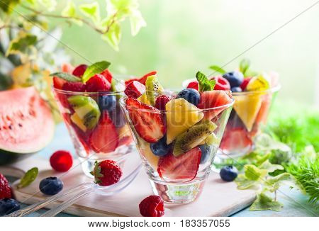 Healthy fresh fruit and berry salad with strawberries, raspberries, kiwi, pineapple, blueberries and watermelon on a table outdoors