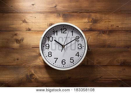 wall clock at wooden background texture