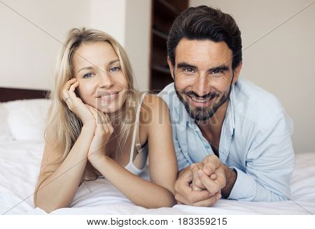 Happy attractive smiling couple lying on bed in bedroom