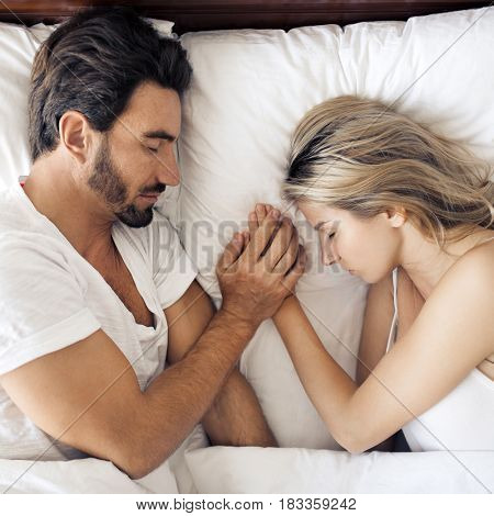 Attractive sleeping couple in bedroom