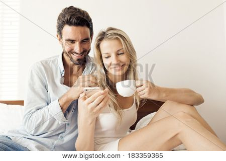 Happy attractive smiling couple sitting on bed in bedroom