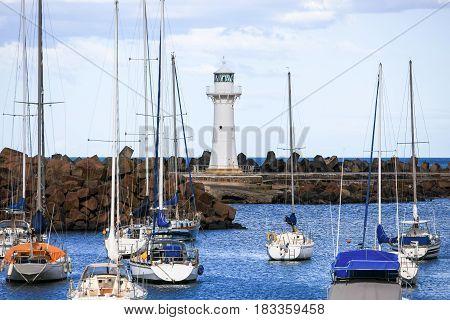 Boats anchored before Wollongong Breakwater Lighthouse, Australia