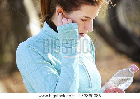 Young woman running outdoor with mobile phone and listening music. Healthy lifestyle concept with equipment.