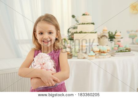 Cute little girl with tasty sweets at party