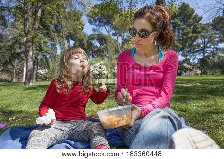 Child And Mother Eating Pasta In Park
