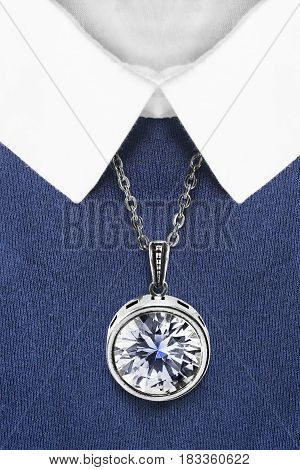 Large crystals pendant over blue pullover with white collar closeup