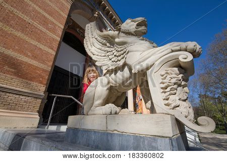 three years old blonde child saluting leaning on winged lion statue outside Palace of Velazquez (from year 1883 by architect Ricardo Velazquez Bosco) in public park El Retiro Madrid Spain