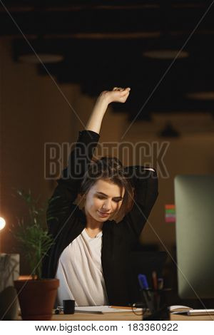 Picture of tired young woman designer sitting in office at night using computer while stretching.