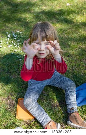 Child Sitting On Grass Teasing With Hands In Eyes