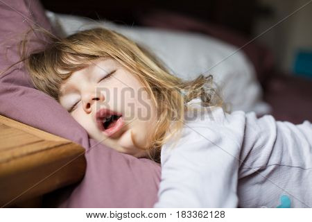 funny face expression with open mouth of blonde caucasian three years old child sleeping on king bed