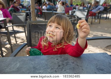 Kid In Terrace Of Cafe Eating Cheese Puff